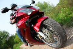 Motorcyclist standing on country road, bottom view royalty free stock images