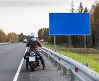 Motorcyclist standing on the highway in front of the blank information board with blue background, autumn season Stock Photography