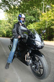 Motorcyclist standing on road royalty free stock photos