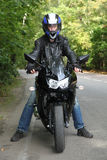 Motorcyclist standing on road stock image