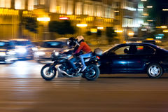 Motorcyclist on street at night stock photo