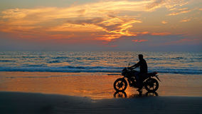 Motorcyclist at sunset on the beach. Stock Photos
