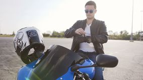 A motorcyclist who sits on a motorcycle in sunglasses and in a leather jacket, wears special leather mitts for riding stock video footage