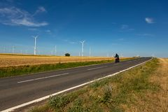 A motorcyclist and wind turbines on the background royalty free stock photo