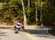 Motorcyclist on a winding road royalty free stock image