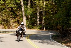 Motorcyclist on a winding road Royalty Free Stock Photography