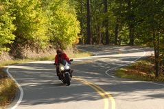 Motorcyclist on a winding road Stock Photography