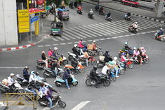 Motorcyclists at a Busy Junction. Motorcyclists wait at a busy junction during rush hour on September 10, 2012 in Bangkok, Thailand. Motorcycles are often the stock images