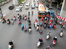 Motorcyclists and cars wait at a junction during rush hour. BANGKOK - NOV 17: Motorcyclists and cars wait at a junction during rush hour on Nov 17, 2012 in royalty free stock photos