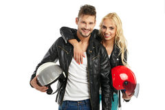 Motorcyclists couple with helmets in hand Stock Images