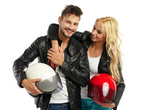 Motorcyclists couple with helmets in hand Stock Photos