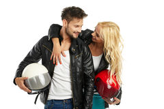 Motorcyclists couple with helmets in hand Stock Image