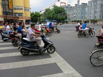 Motorcyclists Crossing the Street. Motorcyclists and cyclists and bike riders cross the street at an intersection in China stock images