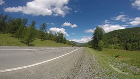 Motorcyclists driving on road stock footage