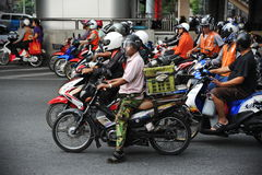 Motorcyclists at a Junction. Motorcyclists wait at a junction during rush hour on November 14, 2012 in Bangkok, Thailand. Motorcycles are often the transport of Royalty Free Stock Images