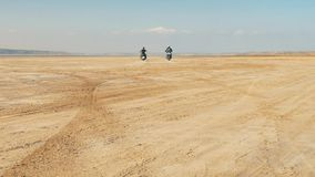 Motorcyclists riding along sandy beach. Bikers ride motorcycle through desert. stock video
