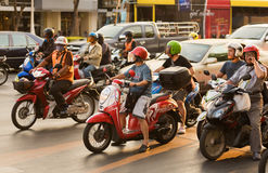 Motorcyclists stand at traffic lights in Thailand Stock Photo