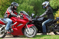 Motorcyclists standing on country road. Two motorcyclists standing on country road, side view, focus on right man royalty free stock photos