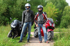 Motorcyclists standing near bikes. Two motorcyclists standing on country road near bikes, where is highway stock photos