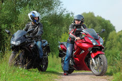 Motorcyclists standing on road looks on each other royalty free stock photos