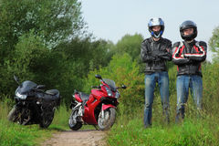 Motorcyclists standing on road near bikes Stock Photo