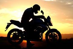 motorcyclistsilhouettesolnedgång Arkivbilder