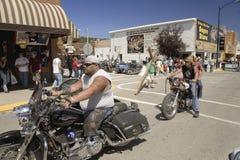 Motorcyclistskörning besegrar den huvudsakliga gatan Royaltyfri Foto