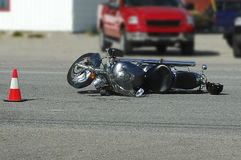 Motorcyclye Accident. Motorcylcle laying on it's side with driver's helmet beside it after being hit by a car