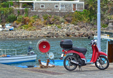 A motorcyclye near the sea front. A photo of a motorcycle on its stand, along the harbour of a sea front with boats in the background Stock Image