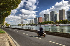 Motorcykel i Paris nära Eiffeltorn med sikt på skyskrapor och floden Arkivbild