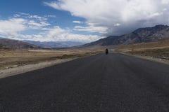 Motorcykel som är rörande på en rak väg i ökenslättar av Ladakh Arkivbilder