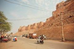 Motorcykel som kör på grusvägen nära det historiska Jaisalmer fortet som byggs i ANNONSEN 1156 i Indien Royaltyfri Bild
