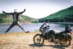 Motorcykelchauffören hoppar med hans utsträckta armar för ett möte av affärsföretag på floden för smutsstrandberg enduro, arkivfoto