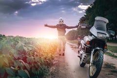 Motorcykelchauffören står med hans utsträckta armar för ett möte av affärsföretag på grusvägsolnedgångtiden enduro, av  arkivfoto
