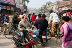 Motorcykelchaufförer, cyklister och gångare flyttar sig på den upptagna fullsatta gatan Arkivbild