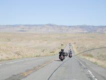 Motorcykelgrupp på en ensam huvudväg arkivbild