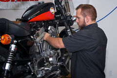 Motorcykelmekaniker som arbetar på den amerikanska motorn Arkivbilder