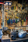 Motorcykeln särar och hjälpmedel på skrivbordet i garage Royaltyfri Foto