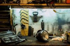 Motorcykeln särar på skrivbordet i garaget Arkivbild