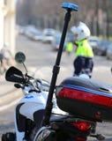 motorcykelpolisen med den blinkande siren och en trafik kommenderar Arkivfoto