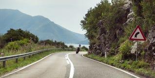 Motorcykelridning ner vägen i riktningen av fjärden Vägen går över kullen Underteckna in förgrunden fotografering för bildbyråer