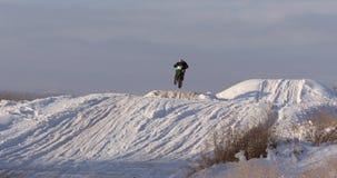 Motorcyklar barncyklistryttare på snöig motocrossspår Ryttare på snö Motocrossryttaren på cykeln, motocross övervintrar stock video