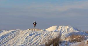 Motorcyklar barncyklistryttare på snöig motocrossspår Ryttare på snö Motocrossryttaren på cykeln, motocross övervintrar lager videofilmer