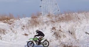 Motorcyklar barncyklistryttare på snöig motocrossspår Ryttare på snö Motocrossryttaren på cykeln, motocross övervintrar arkivfilmer