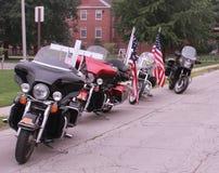 Motorcyklar med flaggor och ett kors på räddningen som vårt kors samlar, Knoxville, Iowa Royaltyfri Bild