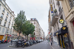 Motorcyklar och bilar som parkeras på gatan Jean-Baptiste Pigalle royaltyfri foto
