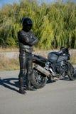 Motorcyklisten i svart bära en hjälm ser en motorcykel royaltyfri fotografi
