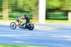 Motorcyklisten rider en gul motorcykel Arkivbilder
