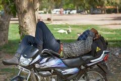 motorcyklisten som sover på en motorcykel i en stad, parkerar arkivfoto