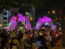 Motorcyklister är på trafikljuset på rusningstiden i centret Staden är dekorerade upplysta bågar royaltyfria bilder